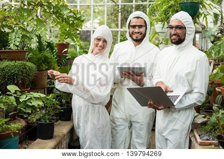 Portrait of happy scientists in clean suit using technologies at greenhouse