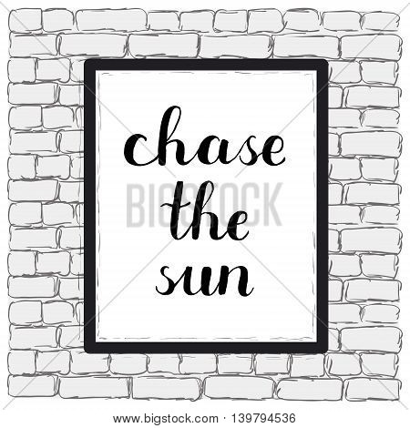Chase the sun. Brush hand lettering on a sample poster hanging on a brick wall.
