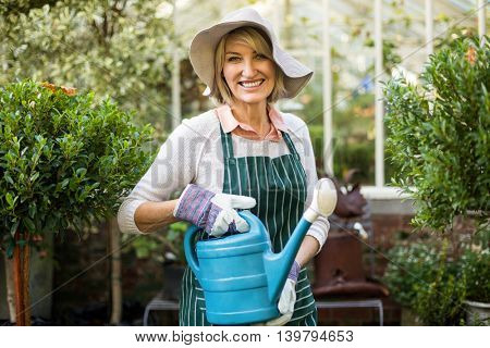 Portrait of female gardener smiling while holding watering can at greenhouse