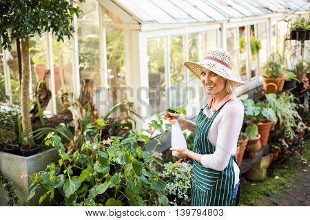 Portrait of happy female gardener watering plants outside greenhouse