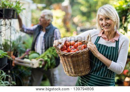Portrait of happy female gardener carrying tomatoes in wicker basket outside greenhouse