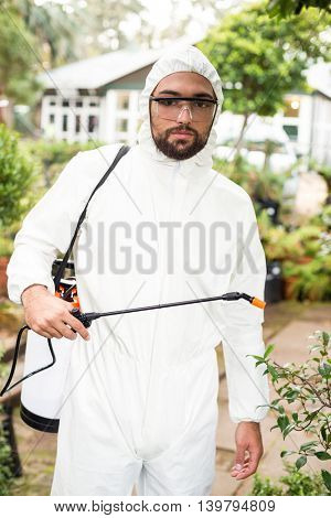 Portrait of male scientist in clean suit spraying pesticides at greenhouse