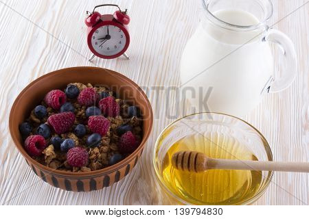 Muesli with fresh berries honey milk and alarm clock on wooden background.