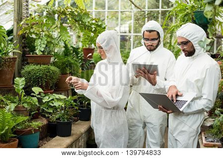 Scientists in clean suit using technologies while examining plants at greenhouse
