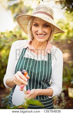 Portrait of woman smiling while watering plants at greenhouse