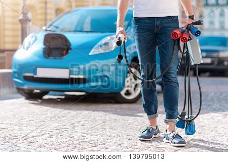 Enjoy new possibility. Close up of a man standing in front of an electric automobile with a lot of power cables in his hands