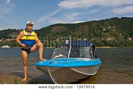 The kind rescuer in a life jacket and his motor boat
