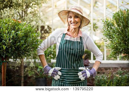 Portrait of confident female gardener with hand on hip standing at greenhouse
