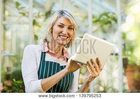 Portrait of happy mature female gardener using tablet computer against greenhouse