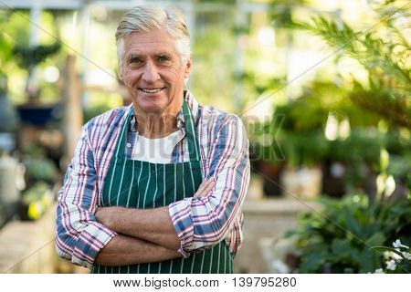 Portrait of confident male gardener with arms crossed against greenhouse