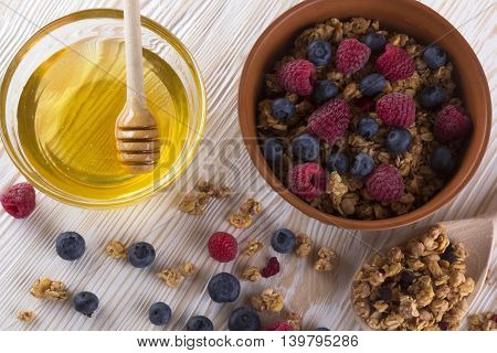 Muesli with fresh berries and honey on wooden background.
