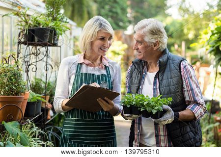 Couple smiling while working outside greenhouse