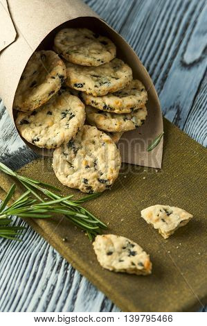 Heap of rosemary and cheese cookies on linen napkin and rosemary branches. Selective focus.