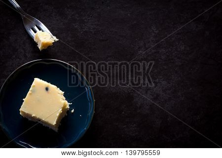 Single Passionfruit Slice on Plate with Fork from Above Dark Background with Copy Space