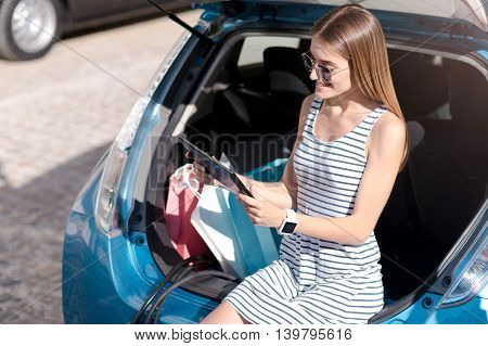 I have to post a photo. Adorable young woman sitting on the trunk of her electric car and using a laptop after shopping