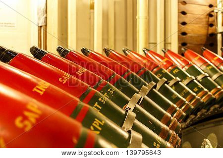 Shot of heavy calibre ammunition shells on an ammunition rack.