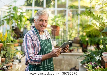 Portrait of male gardener smiling while using digital tablet at greenhouse