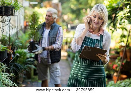 Female gardener talking on mobile phone while man working in background