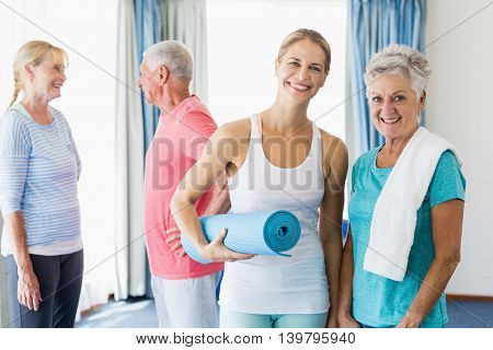 Instructor standing together with seniors during sports class