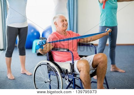 Senior in wheelchair exercising with exercising band during sports class