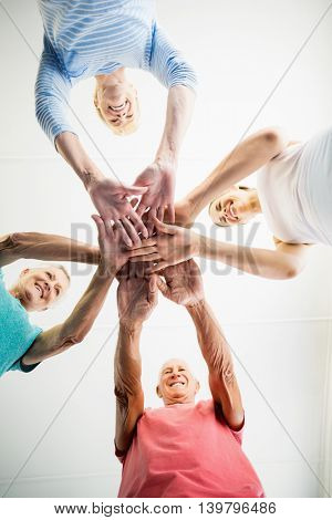 Instructor and seniors putting hands together in a studio