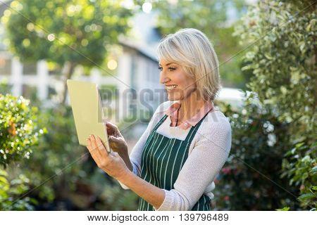 Happy female gardener using digital tablet outside greenhouse