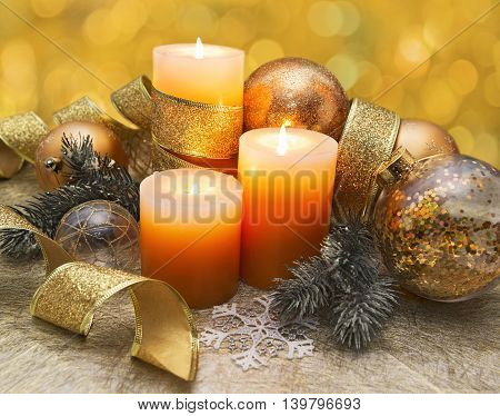 New Year festive still life with three burning candles, conifer branches, golden lace and baubles on yellow background with bokeh lights. Traditional New Year and Christmas celebratory decorations
