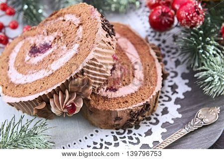 Chocolate rolled cakes with cream and berry jam on wooden plate with white napkin, close up. Christmas and New Year celebratory food still life