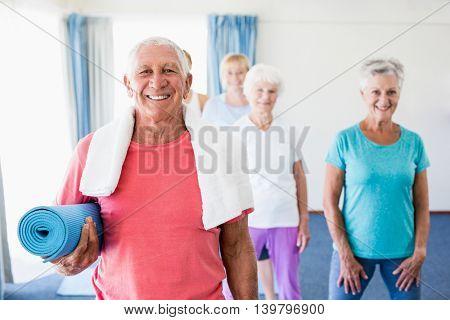 Senior man holding yoga mat during sports class