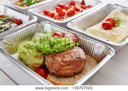 Healthy food background. Take away of natural organic food in foil boxes. Fitness nutrition, meat steak, vegetables and berry cereal. Top view, flat lay.