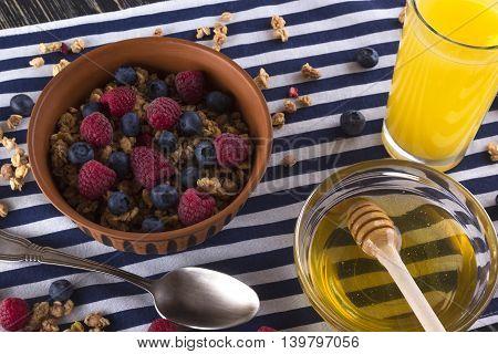 Muesli with fresh berries honey and orange juice on wooden background.