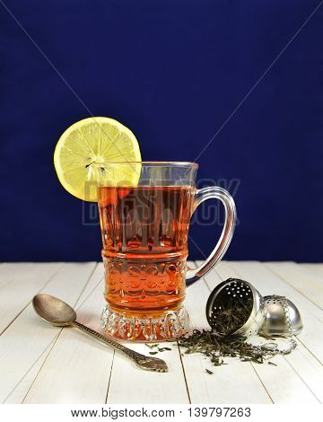Glass cup of cold tea with lemon slice, old spoon and raw tea leaves in strainer on blue background, vintage still life