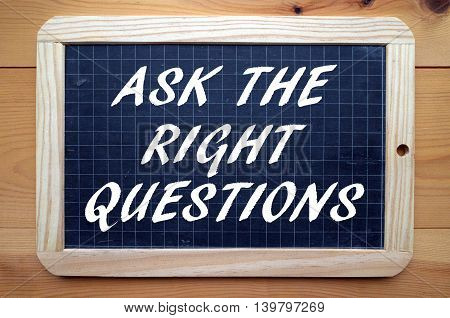 The phrase Ask The Right Questions written in white text on a blackboard as a reminder