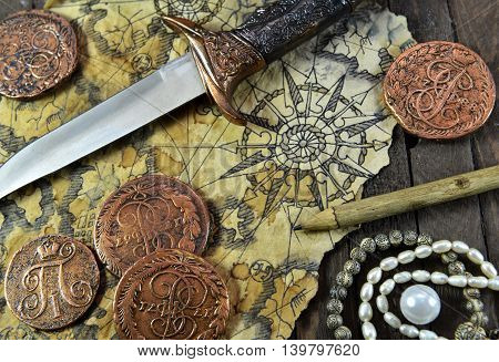 Pirate still life with decorated dagger, map, ancient coins and pearl necklace on wooden background