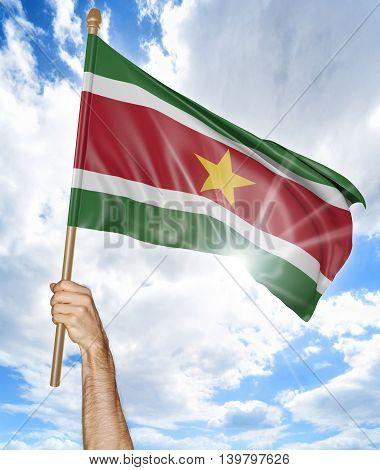 Person's hand holding the Surinamese national flag and waving it in the sky, 3D rendering