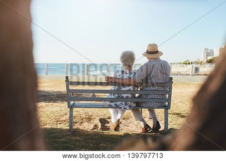 Loving Senior Couple Relaxing On A Bench At The Seaside