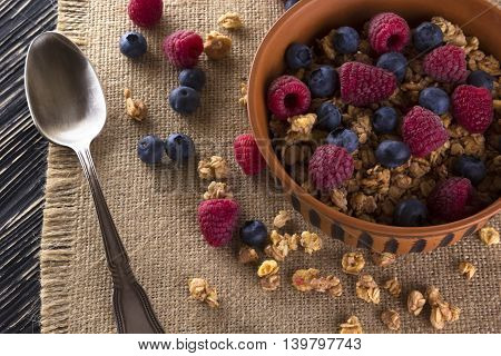 Muesli with fresh berries on wooden background.