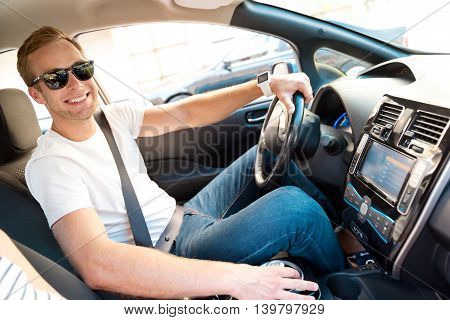 In a good mood. Cheerful mature man looking at the camera while sitting at the wheel of an electric car