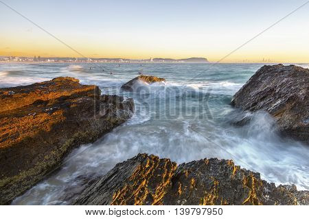 Clear skies sunrise with ocean current over the rocks at Currumbin Rock Gold Coast