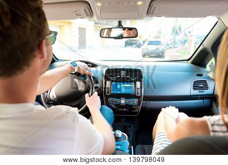 Lets go there. Smiling energetic man driving a car with his girlfriend sitting near him