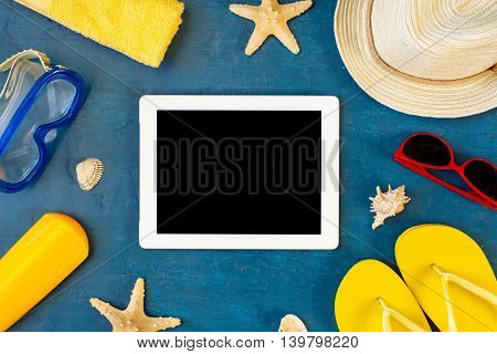 Tablet with blank screen on blue surface with beach items top view