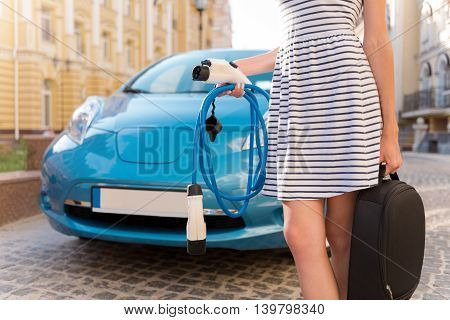 Easy even for me. Close up of a woman standing in front of an electric automobile with a lot of power cables in her hands