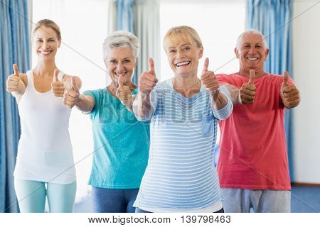 Instructor and seniors with thumbs up in a studio