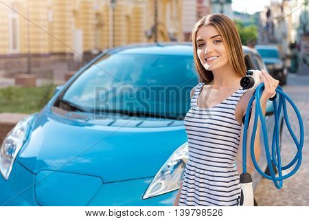 Totally in love with this car. Charming sincere woman holding a power cable to the electric vehicle while standing in front of one