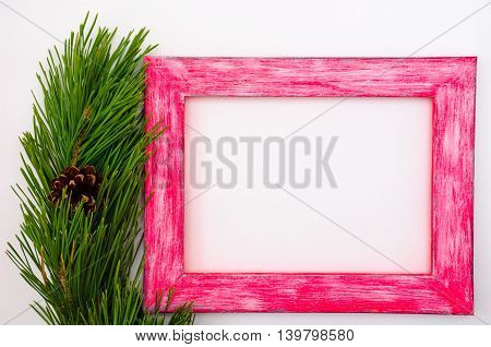 Wooden picture frame with a branch of pine-tree on a white background