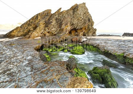 Low tide and green moss on the rocks during sunrise at Currumbin Rock Gold Coast