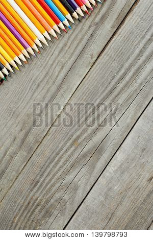 Colored pencils background. Set of colored pencils on wooden background with copy space top view
