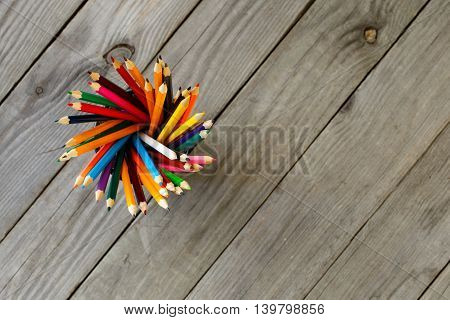 Colored pencils background. Set of colored pencils in the holder on wooden background with copy space top view