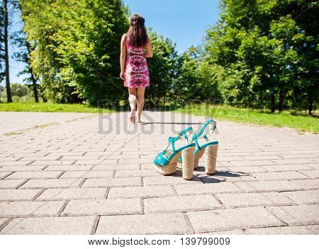 green shoes standing on sidewalk and young woman going away on summer day