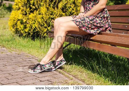 young woman sitting on a park bench on sunny summer day. legs closeup